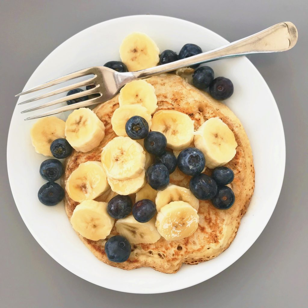 american style pancakes - fruit pancakes with banana and blueberry drizzled in maple syrup