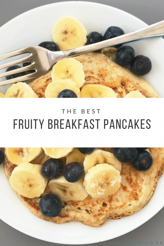"homemade american style pancake topped with bananas, blueberries and maple syrup wit vintage fork on the edge of the white plate. Text overlay saying ""the best fruity breakfast pancakes"""