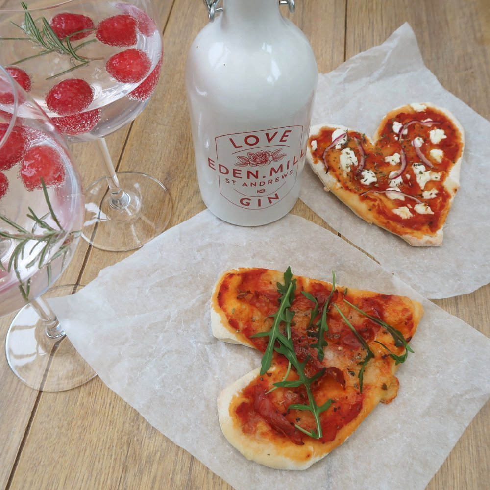 Heart shaped pizza topped with goats cheese and red onions, alongside Eden Mills gin and two gin cocktails garnished with raspberries and fresh rosemary