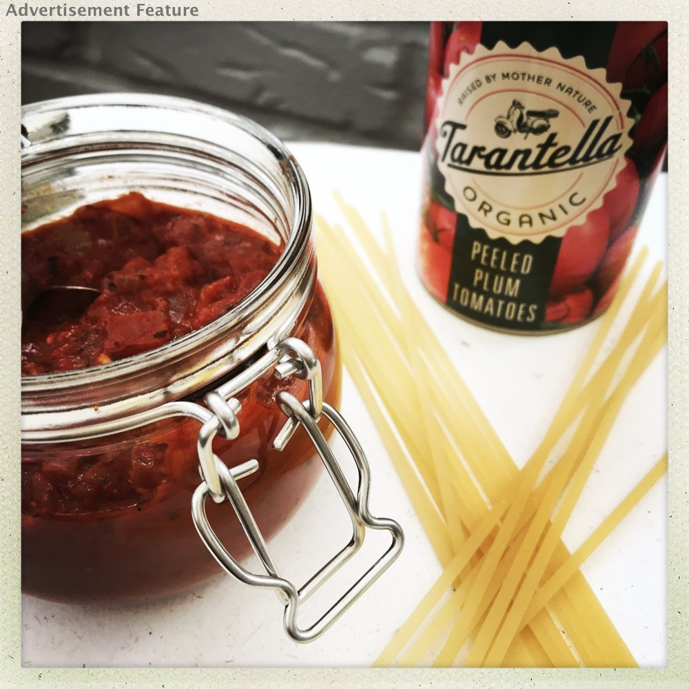 homemade Italian meatball sauce in a glass jar next to a can of Tarantella tomatoes and some dried spaghetti