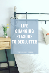 """IKEA black iron bedstead wit fairy lights across the head, blue shell heart hung from the bed post - next to a wooden bedside table with jam jar of flowers and rose quartz crystals. Text overlay saying """" life changing reasons to delutter and life with less"""""""