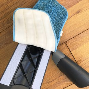 Removable washable fleece head of the ADDIS spray mop after use showing dirt and being pulled off the velcro strips ready to wash
