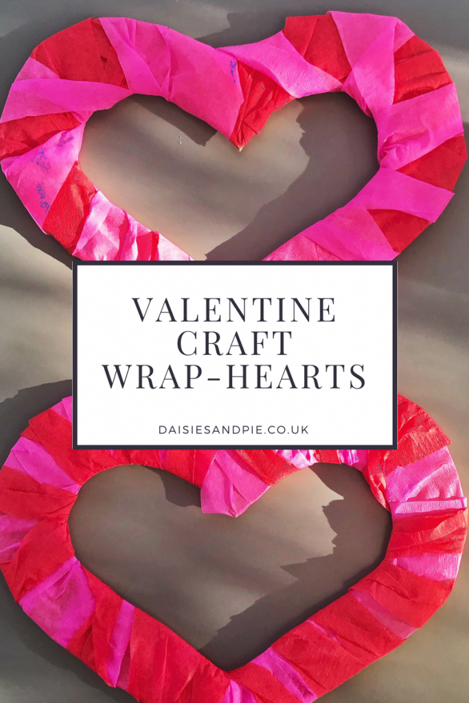"two cardboard hearts wrapped with pink and red crepe paper streamers - text overlay saying ""Valentine Craft Wrap Hearts"""