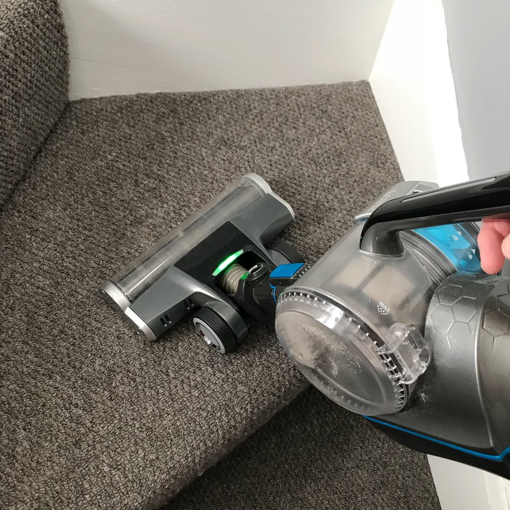 VAX Blade 32V cordless vacuum cleaner with the brush head being used to vacuum the stairs carpet