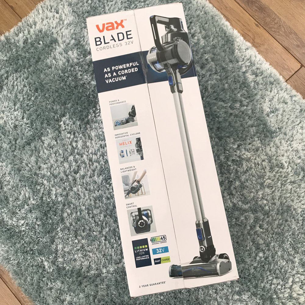 VAX Blade cordless 32V vacuum cleaner in box on a pale blue shaggy rug