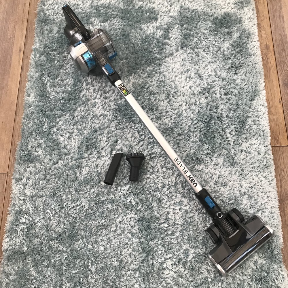 VAX Blade 32V cordless vacuum cleaner lay on a pale blue shaggy rug with a crevice tool and brush tool by the side of it