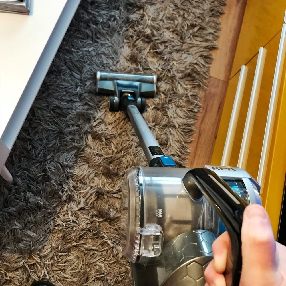 VAX Blade 32V cordless vacuum cleaner being used to clean a brown shaggy rug. Yellow IKEA TV cabinet to the side.