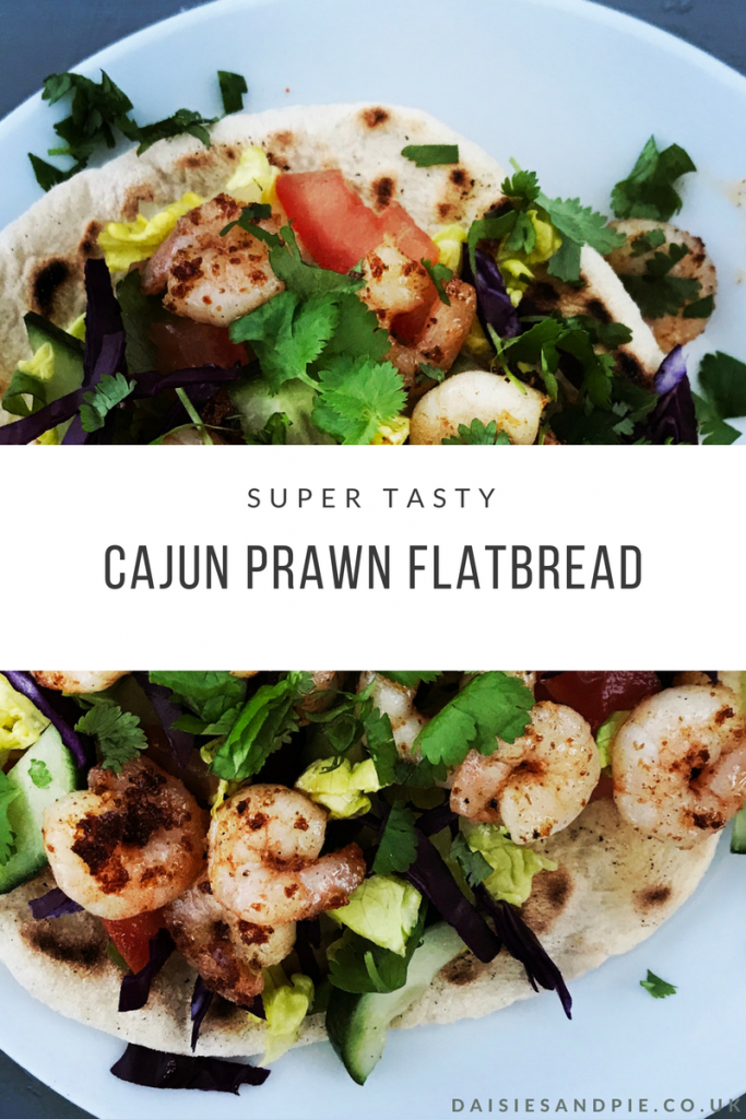 "White plate with freshly made flatbread loaded with salad , topped with Cajun spiced prawns and chopped coriander. Text overlay saying ""super tasty cajun prawn flatbread"""