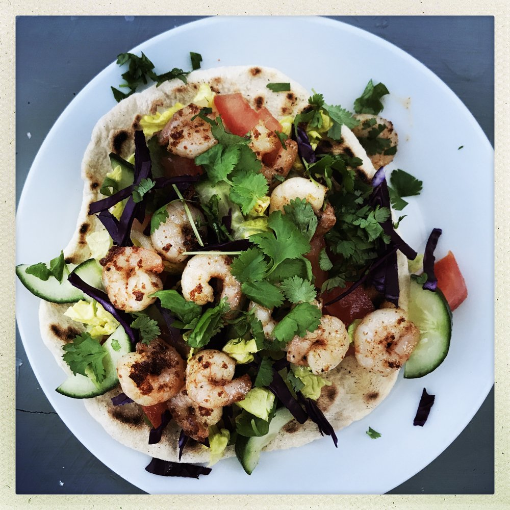 White plate with freshly made flatbread loaded with salad , topped with Cajun spiced prawns and chopped coriander