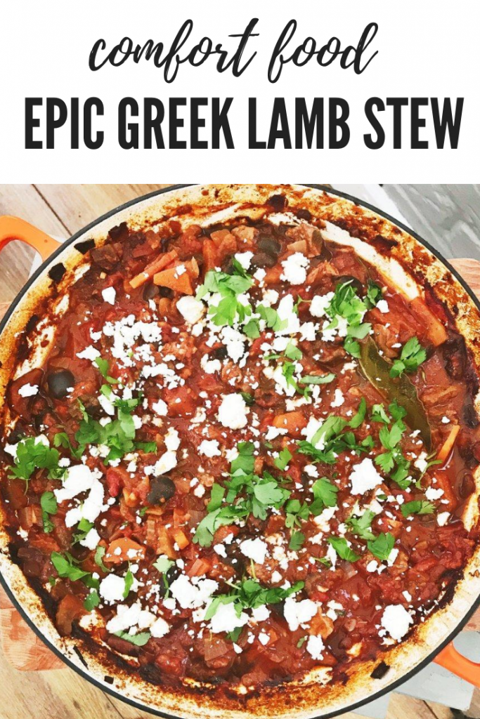 """orange cast iron skillet pan filled with homemade greek lamb stew with tomatoes and olives, scattered with feta cheese and chopped flat leaf parsley. Text overlay """"comfort food - epic greek lamb stew"""""""