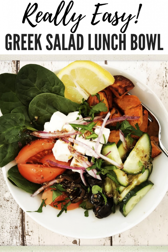 bowl of greek salad with spinach, vine tomatoes, cucumber, black olives, roast sweet potatoes, feta cheese, red onion and balsamic salad dressing. Bowl on a white wooden table. text overlay reads 'really easy! greek salad lunch bowl'