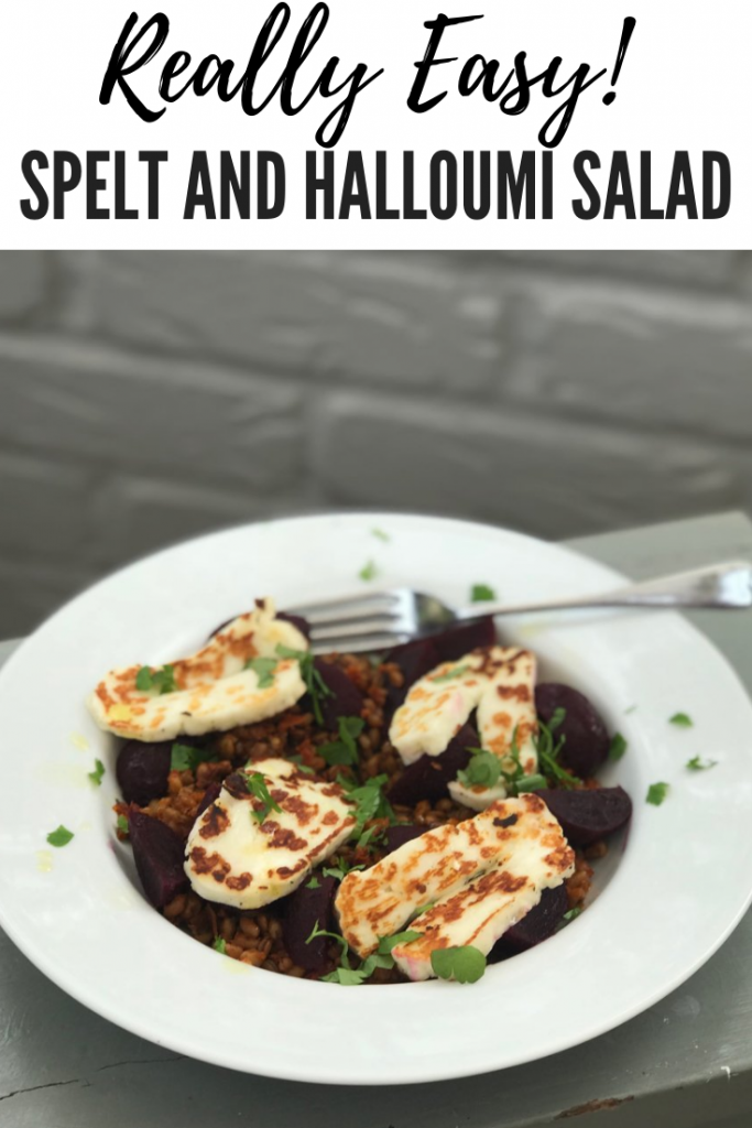 grey painted stool with white plate on top. Plate filled with spelt salad with halloumi and baby beetroot - silver fork on the plate and grey painted brick wall behind. text overlay reads 'really easy! spelt and halloumi salad'