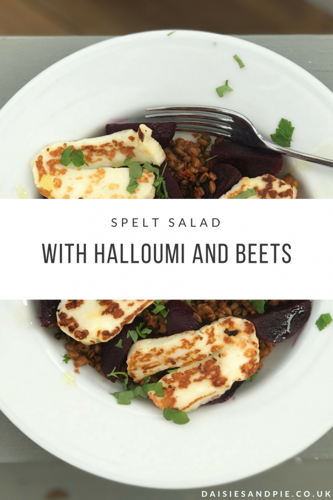 "white plate with merchant gourmet spelt and sun blush tomatoes salad topped with cooked halloumi slices, quarters of baby beetroot and a scattering of flat leaf parsley. Text overlay saying ""spelt salad with halloumi and beets"""