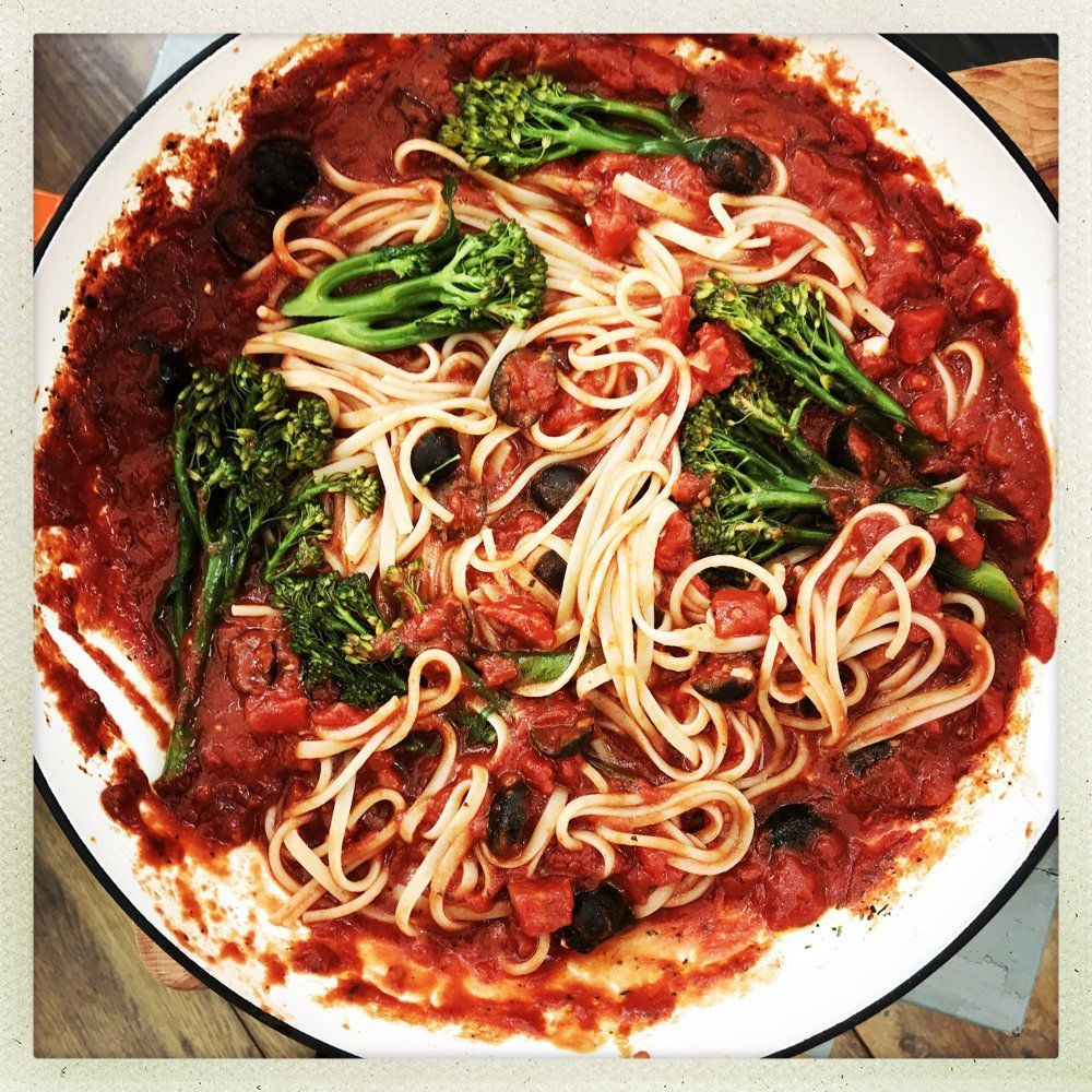 panful of spaghetti in tomato and olive sauce with tender stem broccoli mingled in