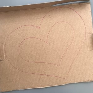heart shape drawn onto cardboard in pink biro