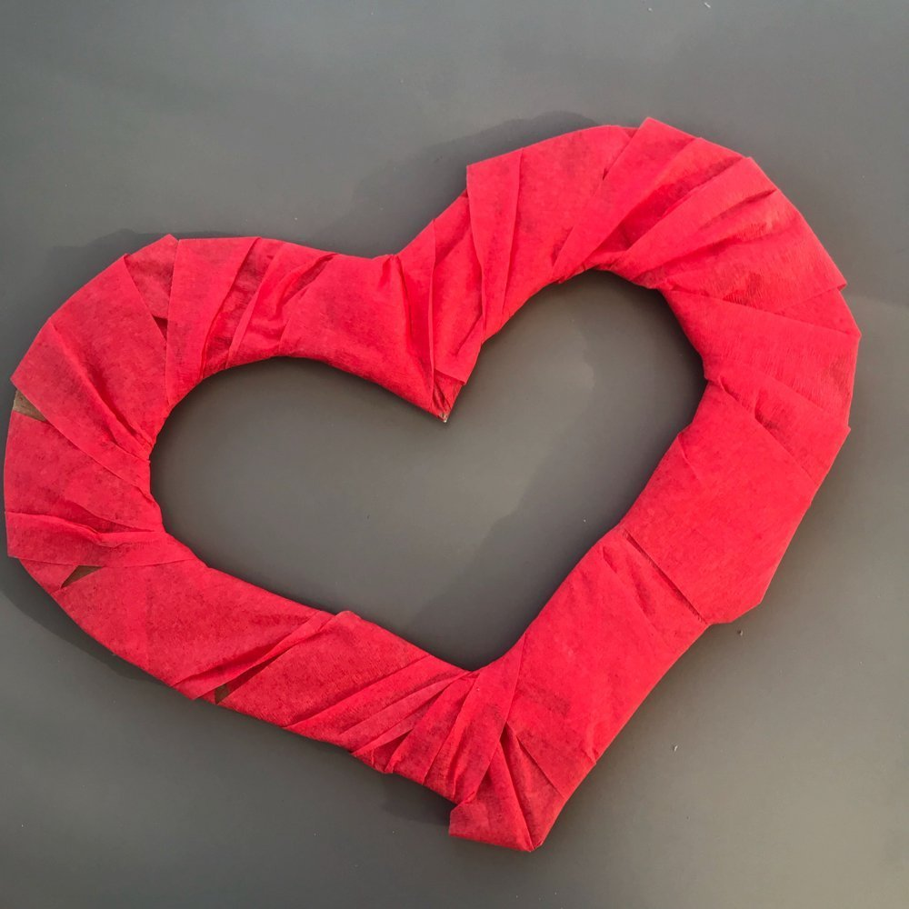 red crepe paper streamer wrapped around a cardboard heart shape