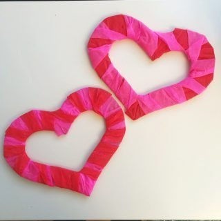 two cardboard heart shapes wrapped with pink and red crepe paper streamers