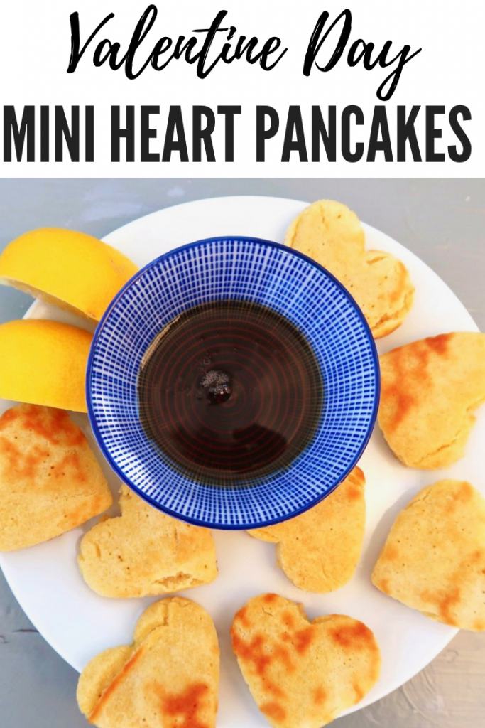 """mini heart pancakes with maple syrup dip and lemon wedges. Text overlay reads """"valentine day mini heart pancakes"""""""