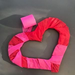 red and pink crepe paper streamer wrapped around a cardboard heart shape