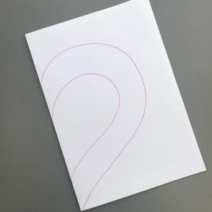 sheet of white A4 paper folded in half with half a heart drawn on it in pink biro