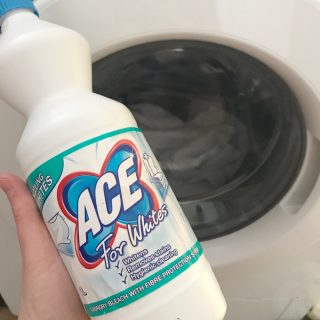 bottle of ACE laundry bleach for whites being held up in front of a washing machine