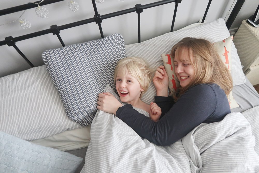 mum and child in bed - IKEA iron bedstead, crisp grey and white striped bedding