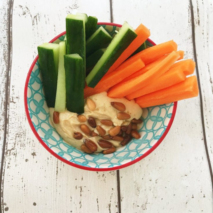 blue and white bowl filled with homemade hummus topped with toasted pine nuts alongside carrot and cucumber batons.