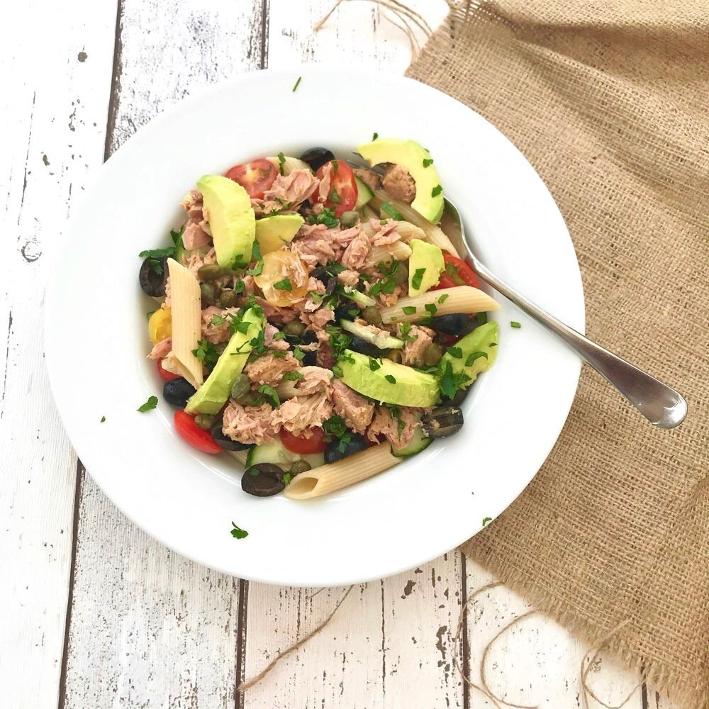 healthy tuna pasta salad with avocado, baby tomatoes and olives served in a white bowl on a hessian cloth