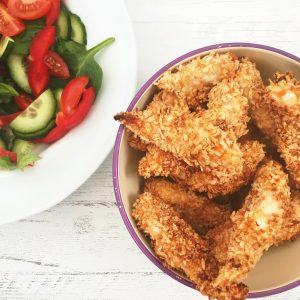 purple and white enamel bowl filled with homemade baked southern fried chicken, bowl of salad by the side