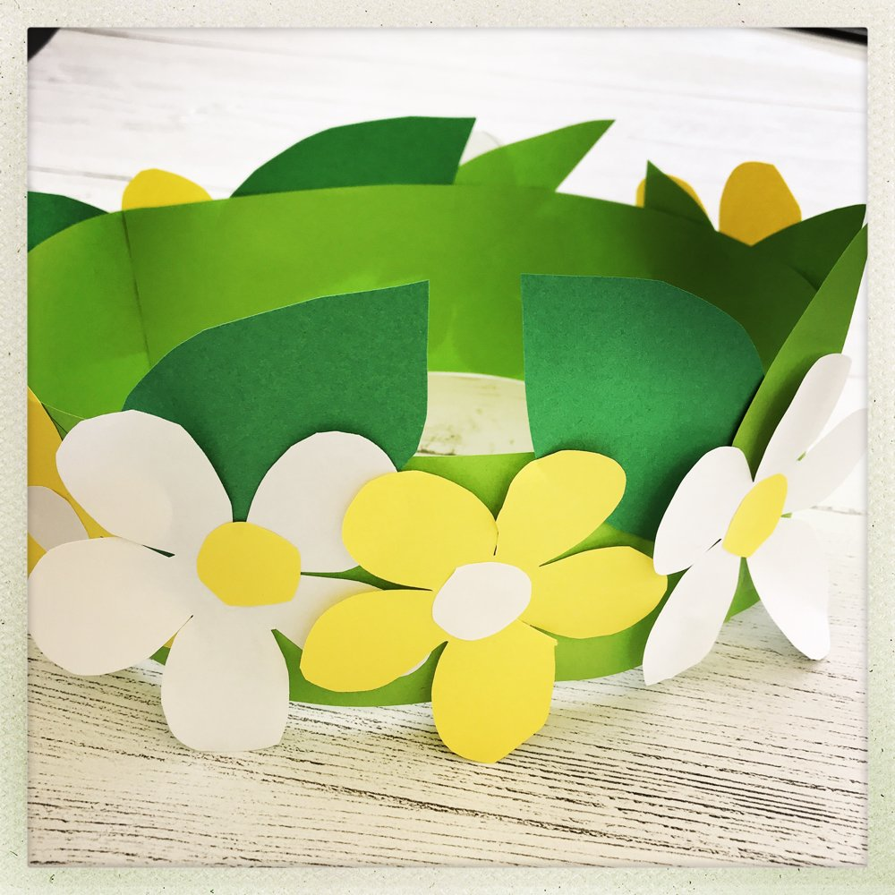 white wooden table with spring paper flower crown made from green, white and yellow paper.