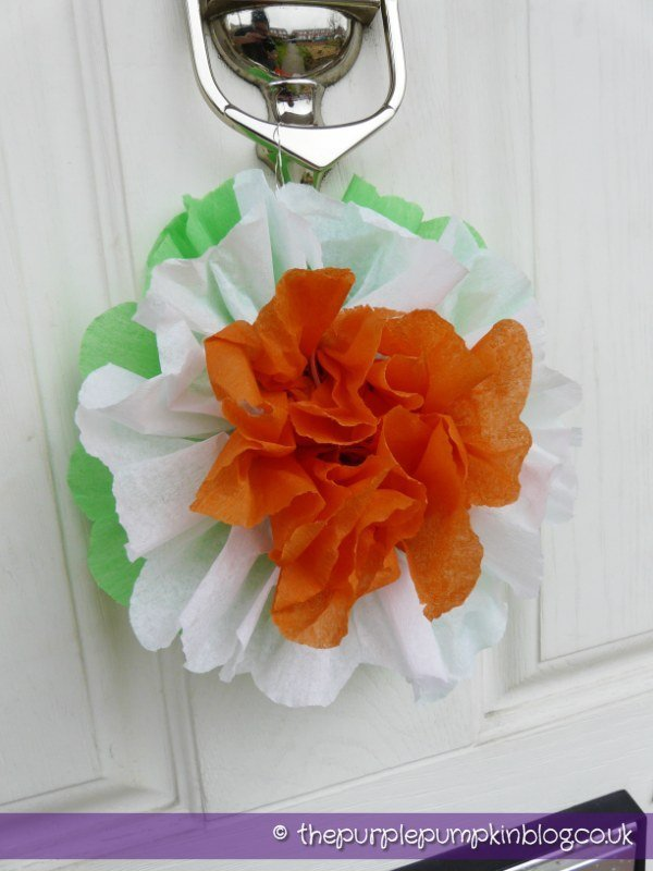 white wooden front door with silver knocker - tied to the knocker is tissue paper rosette in colours of Irish flag - green, white and orange.