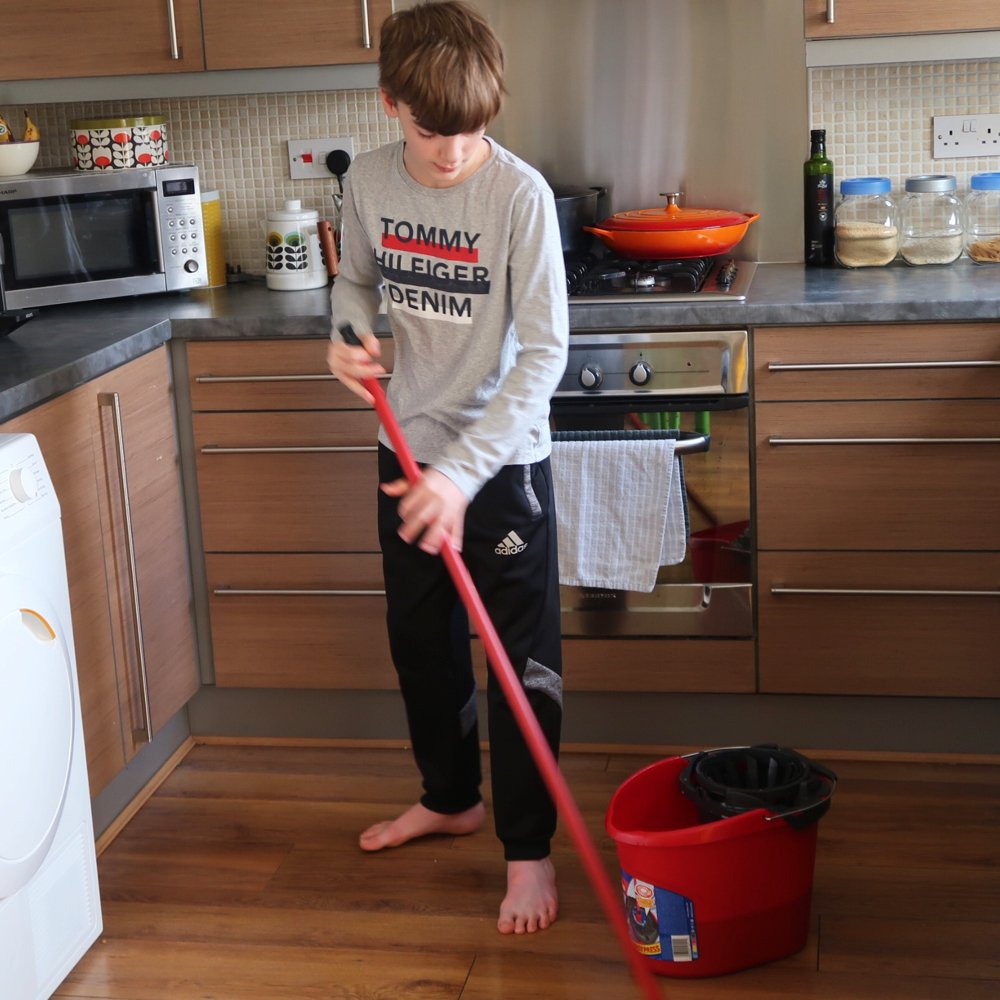 teenage boy doing the mopping in the kitchen with Vileda supermocio mop