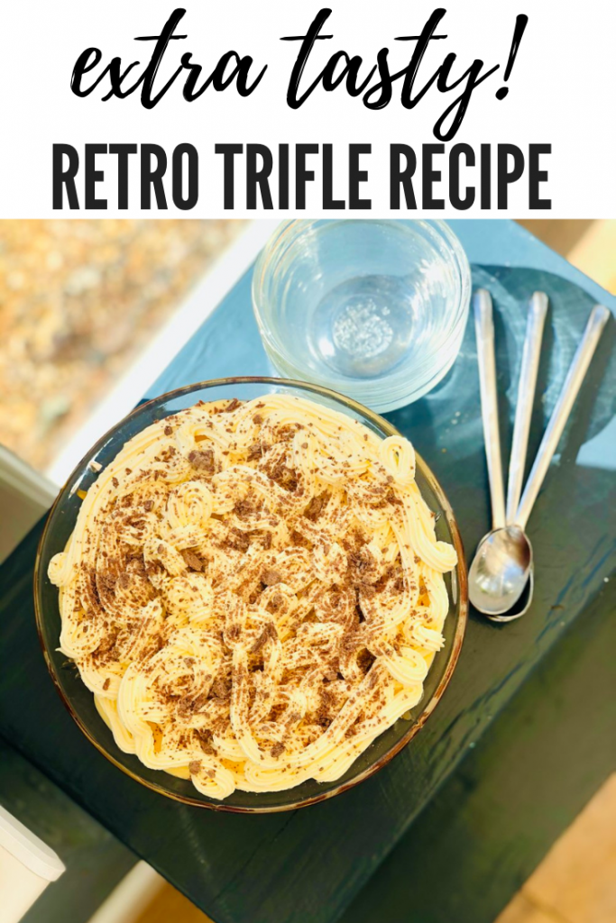 """retro trifle in a cut class bowl with layers of jelly, custard, cream and topped with a chocolate flake. Text overlay """"extra tasty retro trifle recipe"""""""