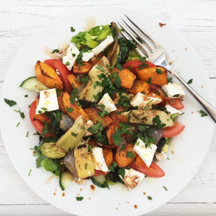 white plate piled high with salad leaves topped with fresh tomatoes, roasted sweet potatoes, roast courgettes, roasted red onions, marinated artichoke hearts, black olives and feta cheese, drizzled with olive oil and balsamic vinegar scattering of flat leaf parsley.