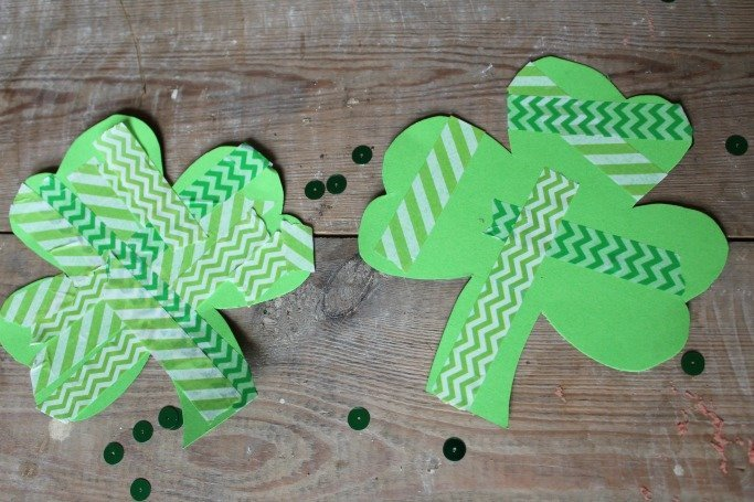 shamrocks cut from green paper and decorated with green patterned wash tape -- shamrocks laid on brown wooden table with shiny green sequins sprinkled around them