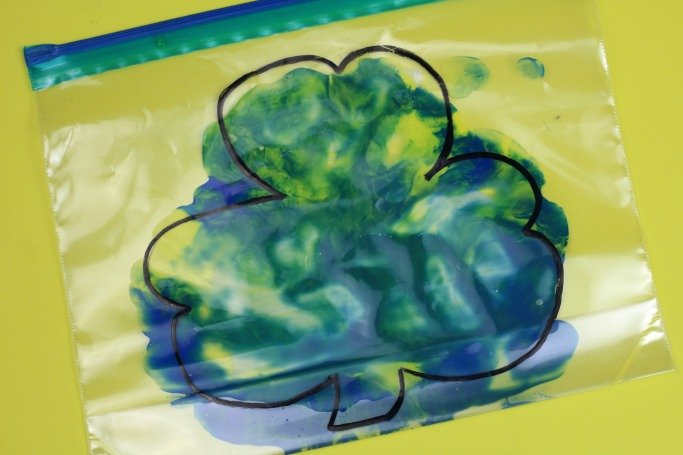 plastic sandwich bag with shamrock drawn on outside of it in marker pen - inside bag is blobs of pain that have been squashed and pressed together to fill shamrock outline