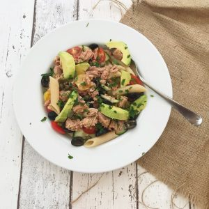 white wooden table with hessian cloth - white plate loaded with tuna and avocado pasta salad