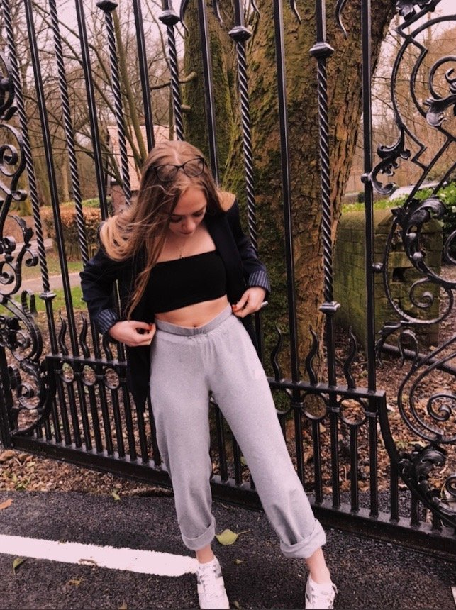 blonde teenage girl wearing the blazer and joggers spring look - photos taken in country park setting with gates, bridges and woods in the backdrops