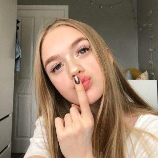 blonde teenage girl wearing impress press on manicure kit nails in metallic rose gold.