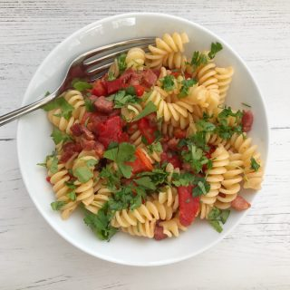 white bowl filled with pancetta and roast pepper pasta sprinkled with chopped flat leaf parsley.
