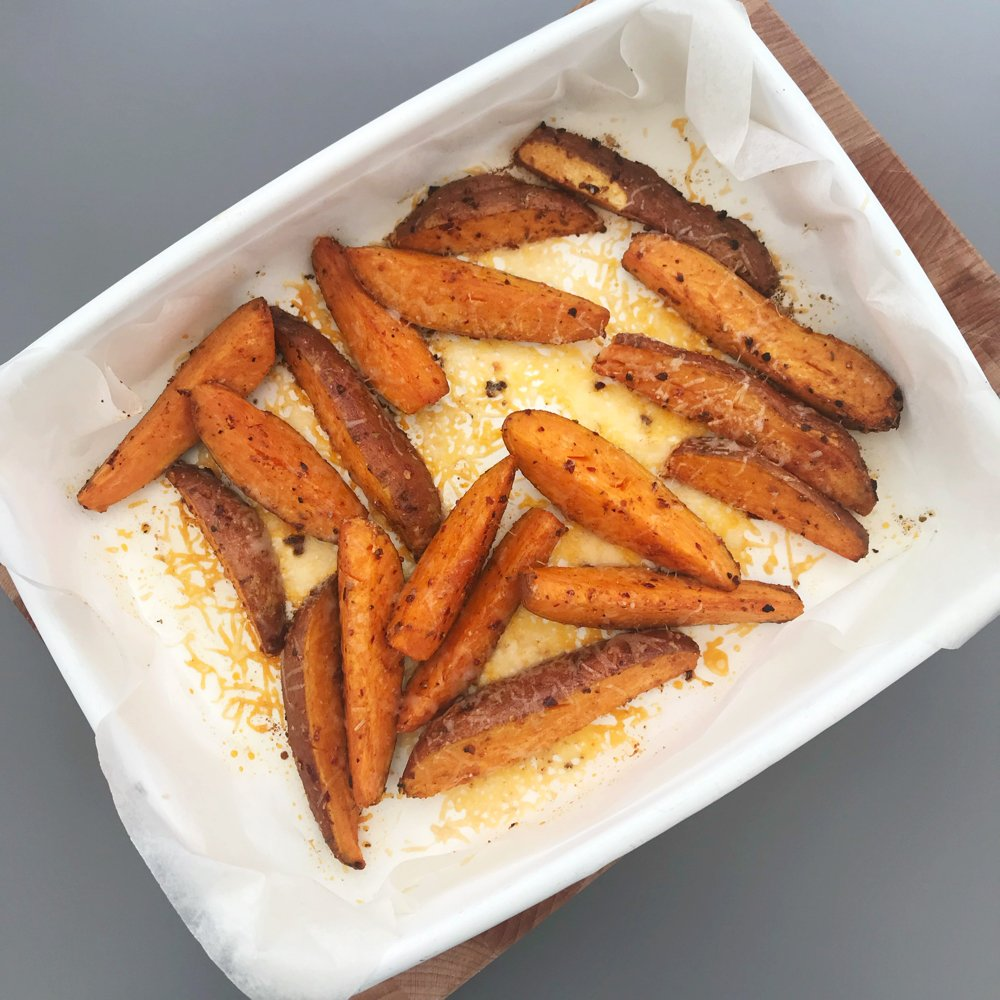 white enamel roasting tin filled with homemade cheesy piri piri sweet potato wedges.