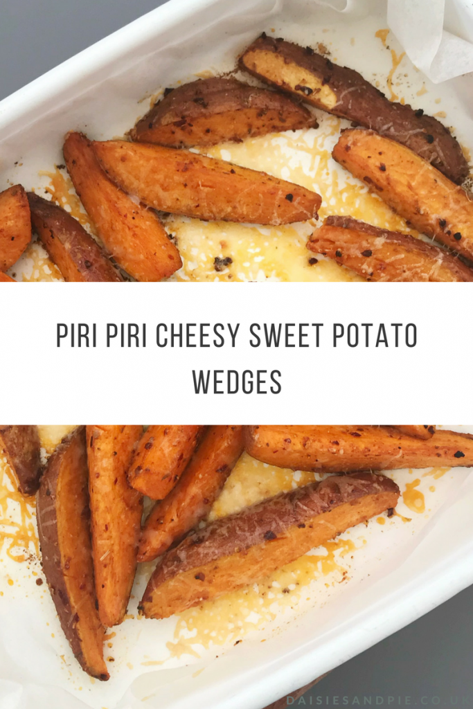 white enamel roasting tin filled with homemade cheesy piri piri sweet potato wedges. Text overlay saying super tasty piri peri sweet potato wedges