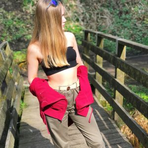 blonde teenage with golden fake tan stood in woods - wearing green combat pants and black crop top.