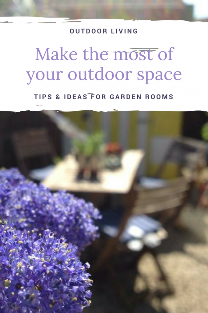 "image of sunny garden with ceanothus blooms, wooden dining table and chairs with beach hut style shed in the background and bunting fluttering in the wind. Text overlay saying ""outdoor living - make the most of your outdoor space - tips and ideas for garden rooms"""