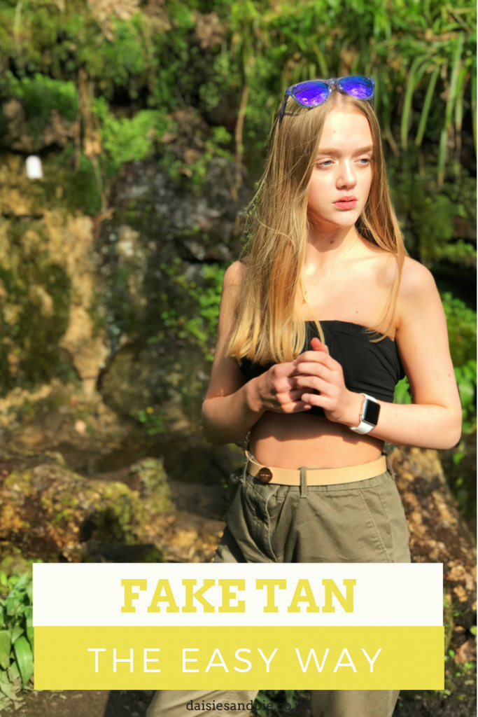 "blonde teenage with golden fake tan stood in woods - wearing green combat pants and black crop top. Text overlay saying ""fake tan the easy way"""