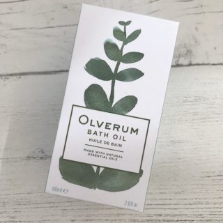 Olverum Bath Oil in the box on a white wooden table