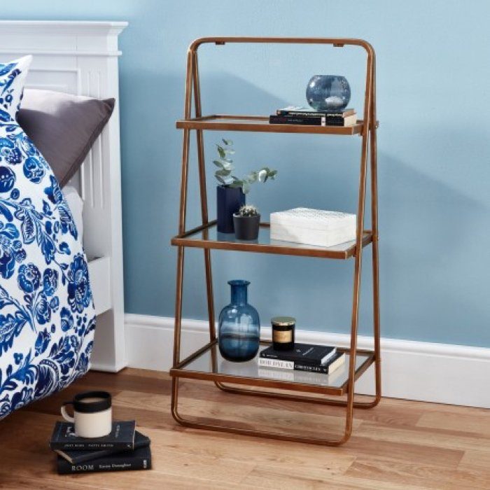 nightstand shelves with bottles, books, tissues and plants