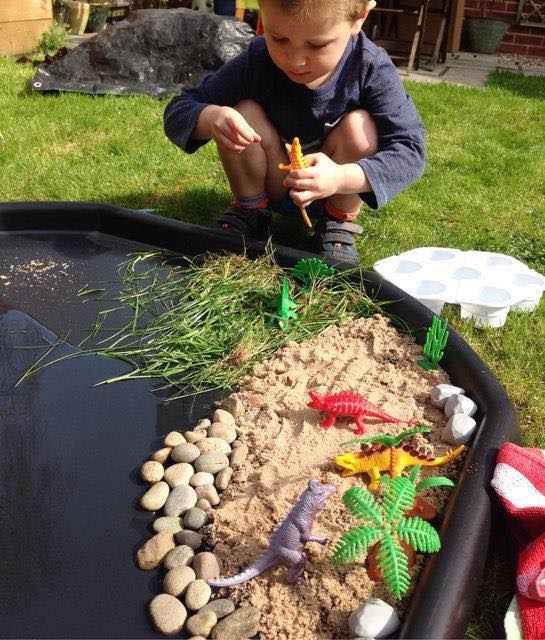 tuff tray set up as a watery dino play scene with small boy playing