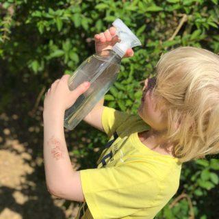 small boy spraying a homemade water gun in the garden