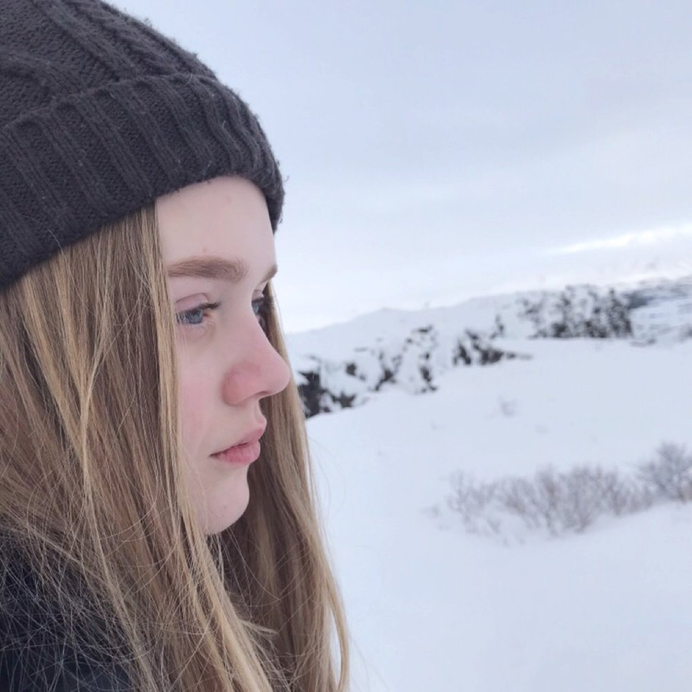 blonde girl wearing beanie stood at the Eurasian tectonic plate and the North American tectonic plate in Iceland